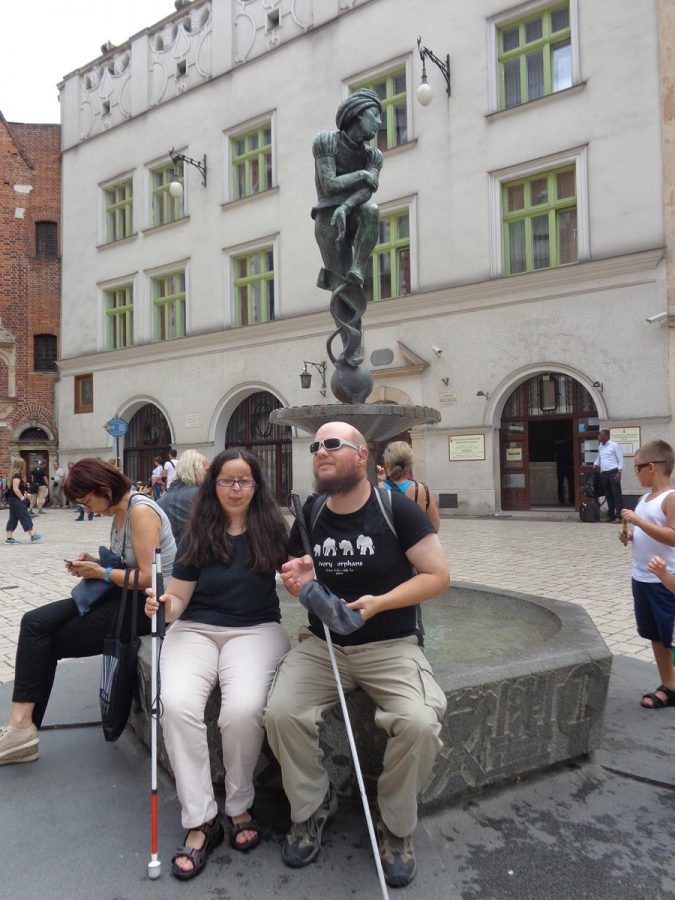 Tony and Tatiana sitting on the side of Zaka Fountain (Fontanna Pomnik Żaka) in Plac Mariacki (Mary's Square). This small fountain has a male bronze figure on a pedestal in the centre and a pool beneath. The fountain was designed by Jan Budziłło and unveiled in 1958. The pedestal is a tribute to Wit Stwosz made by Krakow craftsmen. The Żaczek figure is a copy of one of the figures in the altar of Wit Stwosz in St Mary's Church.