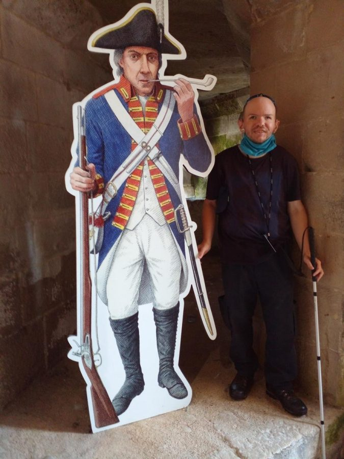 Tony with an 18th century gunnery soldier or musketeer. He has his musket in one hand and is holding a clay pipe in his mouth with the other. He is also carrying a sword. His dress includes a black Tricorne hat, a blue jacket with red and yellow trim, white trousers and long black boots.