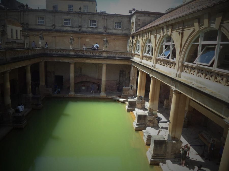 Looking down at the Great Bath from the terrace above. This is the centrepiece of the Roman bath and temple complex located in the city of Bath.  The Great Bath is a rectangular pool measuring 25 metres (82 feet) by 12 metres (39.4 feet) and with a depth of 1.6 metres (5.25 feet). The water comes from a hot spring making it continuously warm at around 35°C. The water's green colour is due to the presence of algae. The surrounding buildings date from the 18th and 19th centuries. Also in view is the colonnade that surrounds the pool  along with the terrace above. Late Victorian statues of Roman emperors look down from the sides of the terrace. In Roman times the pool was covered by an enormous barrel-vaulted roof that rose to a height of 20 metres (66 feet).
