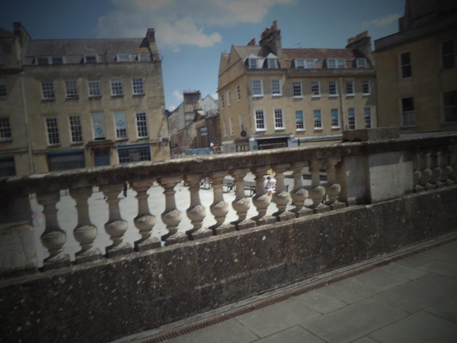 On the terrace above the Great Bath looking over a stone balustrade into Kingston Parade, a public square at the east side of the Roman Baths complex.