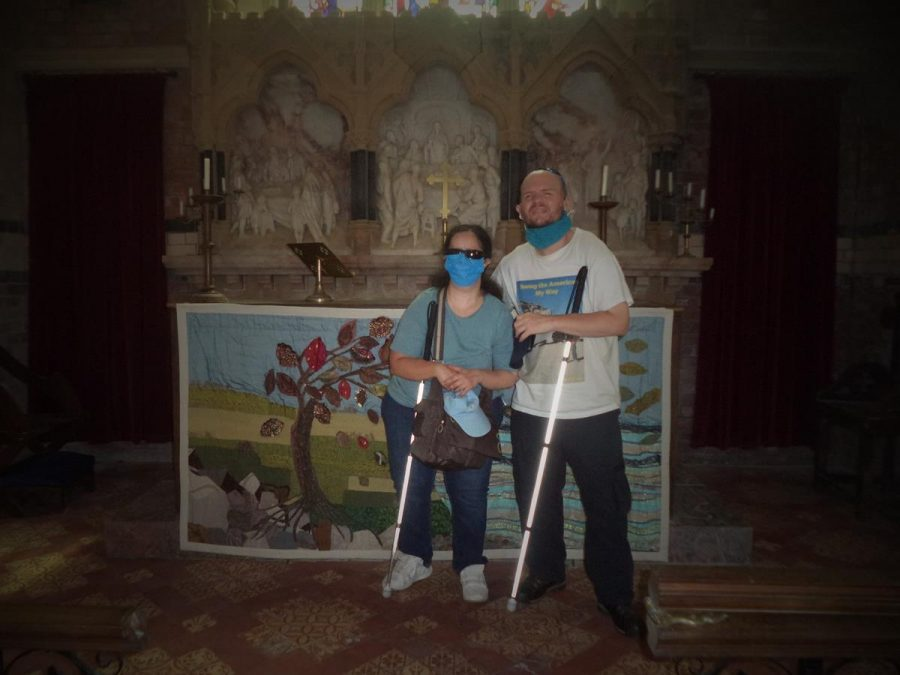Tony and Tatiana inside St. Helen's Church with the main altar behind. In view is a stone altar screen with three alabaster panels depicting the Last Supper and beneath a large hand-made crochet tapestry depicting the landscape on Lundy. The tapestry shows the sea, rocks and grass, along with a single tree bent by the wind, all in a stylised design.