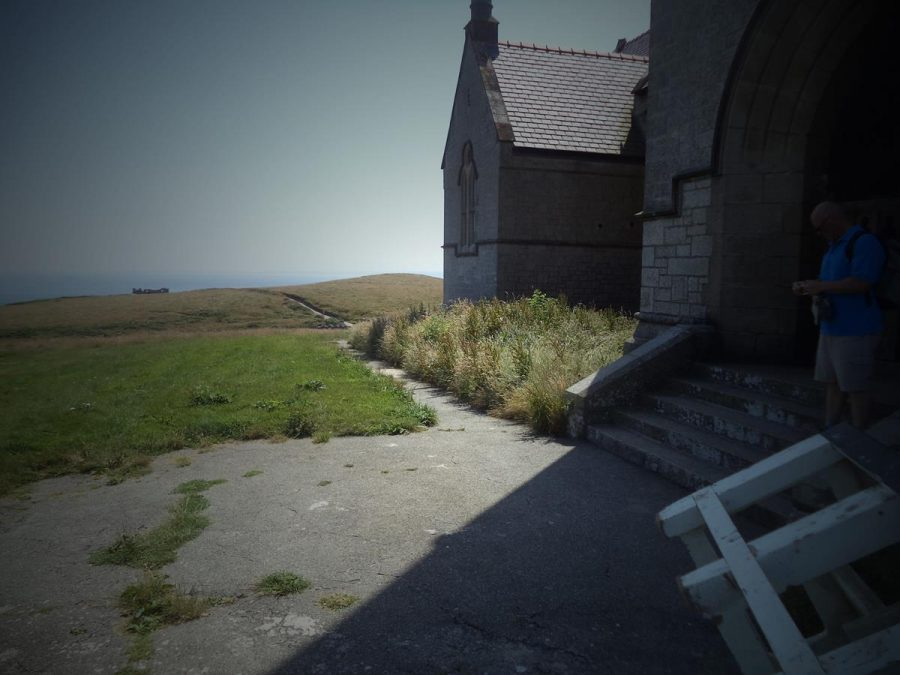View from outside St. Helen's Church showing the rolling grassy landscape with the sea extending to the horizon beyond.