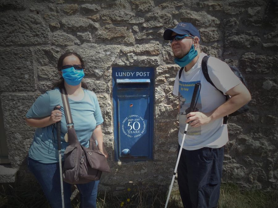 This image has an empty alt attribute; its file name is DSC09041-900x675.jpgTatiana and Tony in front of a blue Lundy Post box in a stone wall. Since 1929 Lundy has issued its own postage stamps due to there being no official Royal Mail post boxes on the island. The stamps, which often depict puffins, can be bought at Lundy Post Office. The stamps pay for transportation to the mainland where Royal Mail stamps are also attached.