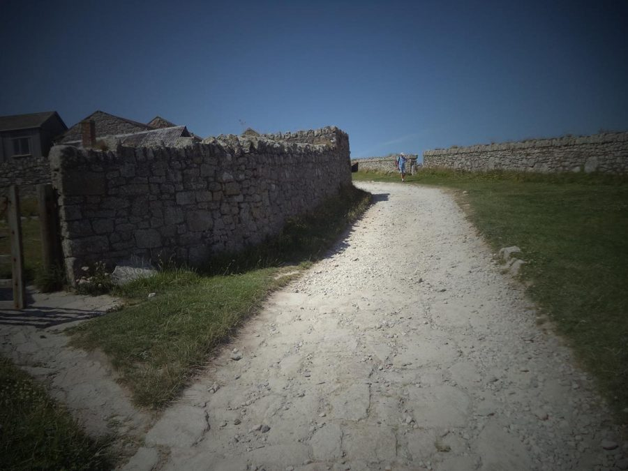 A gravel track lined with stone walls close to the Marisco Tavern.
