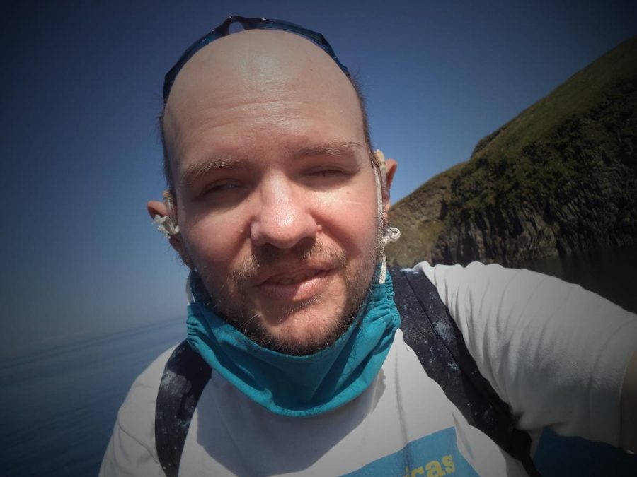 Selfie of Tony with sea and cliffs behind.