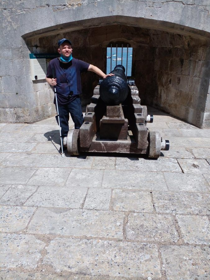 Tony touching a large cannon on the lower gunnery platform. The cannon is pointing through a gun opening in the ramparts towards Portland Harbour, which it was intended to protect.