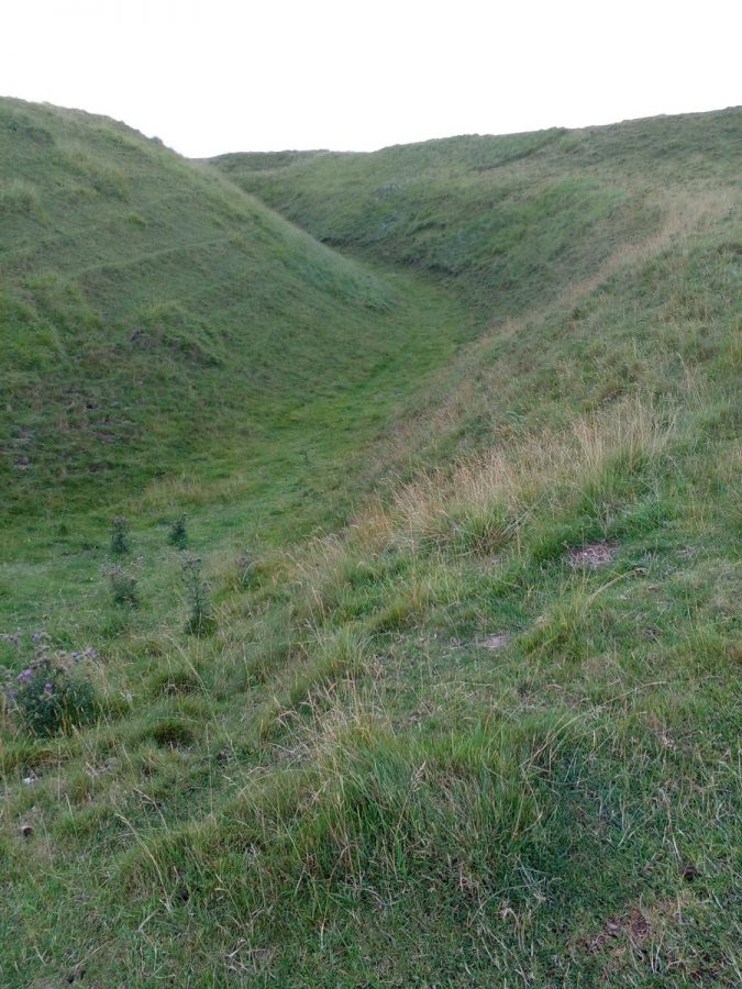 Maiden Castle showing parts of the series of grass-covered mounds and ditches which today make-up the site. When constructed, these ramparts would have been bare white chalk. Tony climbed up the steep hill to reach this point at the top.