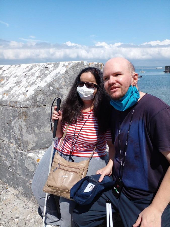 Tatiana and Tony sat on the parapet wall of Portland Castle with the harbour in the background.
