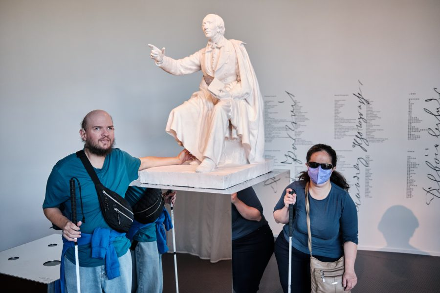 This image has an empty alt attribute; its file name is DSCF3459-900x600.jpg Tony and Tatiana next to a statue of Hans Christian Andersen inside the Hans Christian Andersen Museum (or the H.C. Andersen House) in Odense. Although the house is semi-separate from the exhibitions. Andersen is depicted holding a book and with his other arm held aloft. He is looking and pointing at something in front of him. The statue is placed on a mirrored plinth.