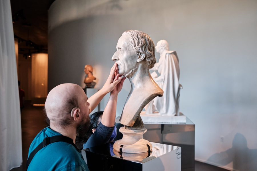 Tatiana and Tony touching the face of the Hans Christian Andersen bust.