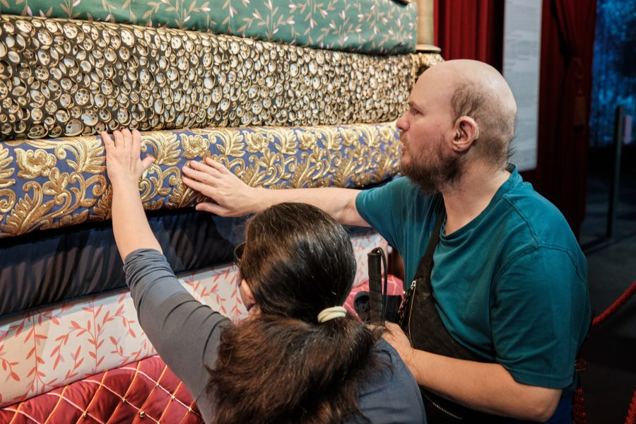 Tony and Tatiana touching a high stack of mattresses, which are all decorated in different colours and with pretty patterns. This is based on the Hans Christian Andersen fairy tale titled The Princess and the Pea. A story about a young woman whose royal identity is established by a test of her sensitivity.