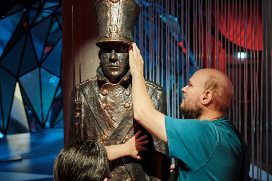 Tony and Tatiana touching a life-sized metal statue of a soldier who is holding a bayonet and wearing a tall hat. This is from the fairy tale titled The Steadfast Tin Soldier which is about atin soldier's love for a paperballerina. It's unclear if this statue has only one leg or two!