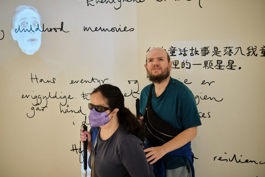Tony and Tatiana passing by a wall inside the Hans Christian Andersen Museum. The wall is white and is decorated with large handwritten messages written in various languages.