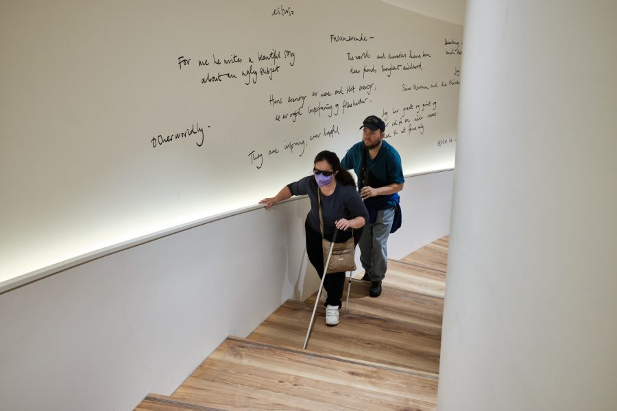 """Tatiana and Tony climbing a curved staircase. The wall alongside has comments about Hans Christian Andersen's work written on it in large handwritten lettering. Examples include """"The words and characters have been dear friends throughout childhood"""" and """"For me he writes a beautiful story about an ugly subject""""."""