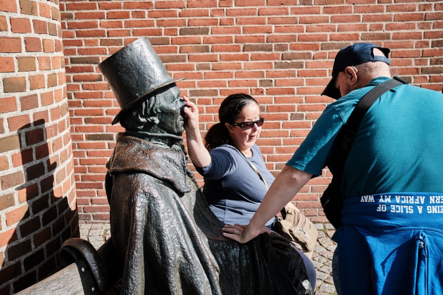 Tony and Tatiana touching a bronze statue of Hans Christian Andersen sitting on a bench outside the Radisson Hotel, located on Claus Bergs Gade 7 in the Old Town.