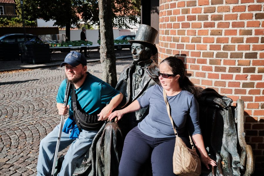 Tony and Tatiana sitting on the Hans Christian Andersen bench. Andersen is sitting in the middle wearing an overcoat and top hat. He's made of metal and has a case with him that is out of view. The statue was created by Danish artist, Jens Galschiøt.